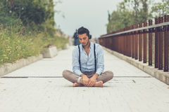 Young handsome man listening to music in an urban context Royalty Free Stock Photography