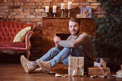 A young handsome man looking at a camera while sitting on a floor surrounded by gifts royalty free stock image