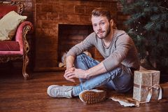 A young handsome man looking at a camera while sitting on a floor surrounded by gifts royalty free stock photo