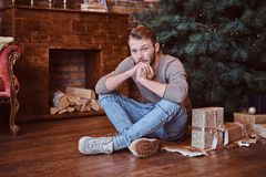 A young handsome man looking at a camera while sitting on a floor surrounded by gifts stock images