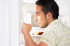 Young handsome man looking for food in the fridge Stock Photo
