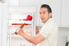 Young handsome man looking for food in the fridge Royalty Free Stock Images
