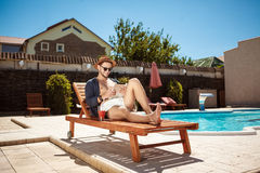 Young handsome man looking at tablet, sitting near swimming pool. Royalty Free Stock Images