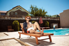 Young handsome man looking at tablet, sitting near swimming pool. Royalty Free Stock Photo