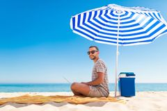 Free Young Handsome Man Lusing Laptop Computer On Beach Bench With Blue Solar Umbrella Overhead, Surrounded By Turquoise Sea And Stock Photos - 133343763
