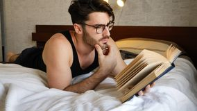 Young man lying in bed and reading a book. Young handsome man lying in bed and reading a book in his bedroom at home Royalty Free Stock Photos