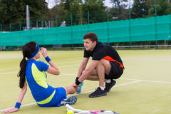 Young handsome man massaging woman`s injured leg after tennis ma. Young handsome men massaging woman`s injured leg after  tennis match on a court outdoor in Stock Images
