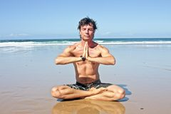 Young handsome man meditating on the beach Royalty Free Stock Photography
