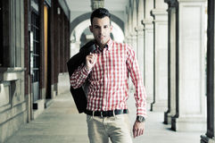 Young handsome man, model of fashion in the street. Portrait of a young handsome man, model of fashion, wearing jacket and shirt in urban background Royalty Free Stock Images