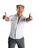 Young handsome man in modern cap showing ok sign Royalty Free Stock Photos