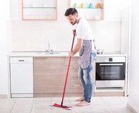 Man mopping floor in kitchen. Young handsome man mopping tiled floor in kitchen. Husband housework concept Stock Photo