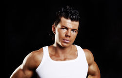 Young handsome man with muscles over dark Royalty Free Stock Images