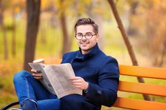 Young handsome man with newspaper sitting on bench. In park Stock Photo