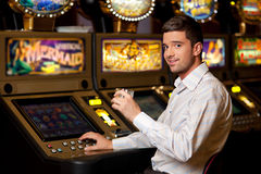 Young handsome man next to slot machine. Young handsome man playing the slot machine holding drink Royalty Free Stock Photography