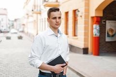 Young handsome man with a notebook in a white shirt. On the street Royalty Free Stock Image