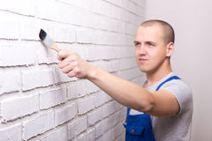 Young handsome man painter in workwear painting brick wall with Stock Images