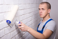 Young handsome man painter in workwear painting brick wall with Royalty Free Stock Images