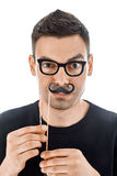 Young handsome man with paper moustaches and glasses making face Royalty Free Stock Photos