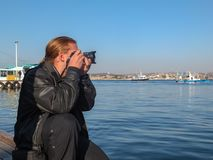 Young handsome man photographer with blond long hair in black leather jacket against blue Black sea photographs sea bay. stock photo