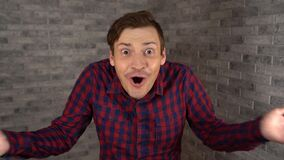 A young handsome man in plaid shirt opens his mouth and spreads his hands from surprise on a gray brick background.