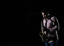 Young handsome man playing music on saxophone Royalty Free Stock Image