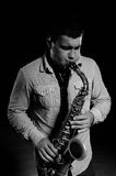 Young handsome man playing music on saxophone Stock Images
