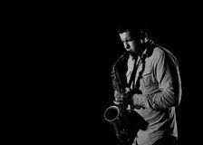 Young handsome man playing music on saxophone Royalty Free Stock Photo