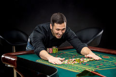 Young handsome man playing roulette wins at the casino Stock Photos