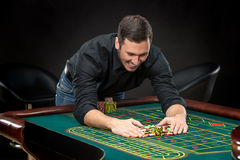 Young handsome man playing roulette wins at the casino Royalty Free Stock Image