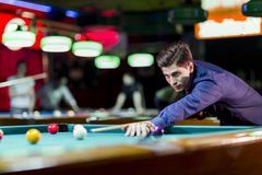 Young handsome man playing snooker. Young handsome man leaning over the table while playing snooker Stock Photo