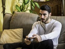 Man playing video game and talking with online players. Young handsome man playing video game and talking with online players through headset, while sitting on Royalty Free Stock Images