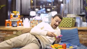 Adult man plays with kid constructor in children`s room in cafe stock video