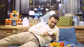 Funny adult man plays with kid constructor in children`s room in cafe stock footage