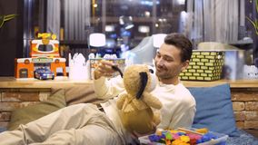 Adult caucasian man plays with toy dog in the children`s room in cafe stock footage