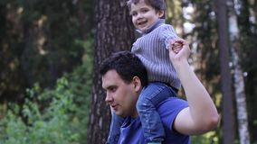Young handsome man plays with his little son stock video footage