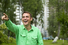 A young handsome man points his finger to the side Royalty Free Stock Images