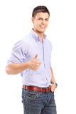 Young handsome man posing and giving a thumb up Royalty Free Stock Images