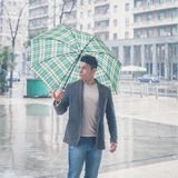 Young handsome man posing with umbrella Stock Image