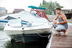 Young handsome man preparing boat to start a journey Royalty Free Stock Images