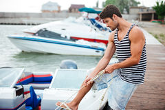 Young handsome man preparing boat to start a journey Stock Photography