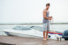 Young handsome man preparing boat to start a journey Royalty Free Stock Photos