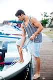 Young handsome man preparing boat to start a journey Royalty Free Stock Image