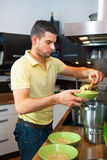 Young handsome man preparing lunch Stock Images