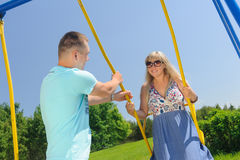 Young handsome man pushing his girlfriend on a swing. Couple having fun on the swing. Amorous couple on romantic date on swings outdoor. Love, relationship Royalty Free Stock Photography