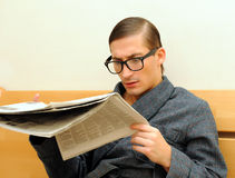 Young handsome man reads newspaper Royalty Free Stock Photography
