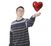 Young handsome man with red heart balloon. Over white Stock Photography
