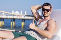 Young handsome man relaxing on the beach Royalty Free Stock Image