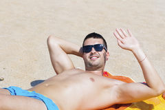 Young handsome man relaxing on the beach and waving Stock Photos