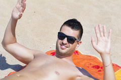 Young handsome man relaxing on the beach and waving Royalty Free Stock Images