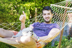 Young handsome man Relaxing In Hammock with his dog Royalty Free Stock Photography